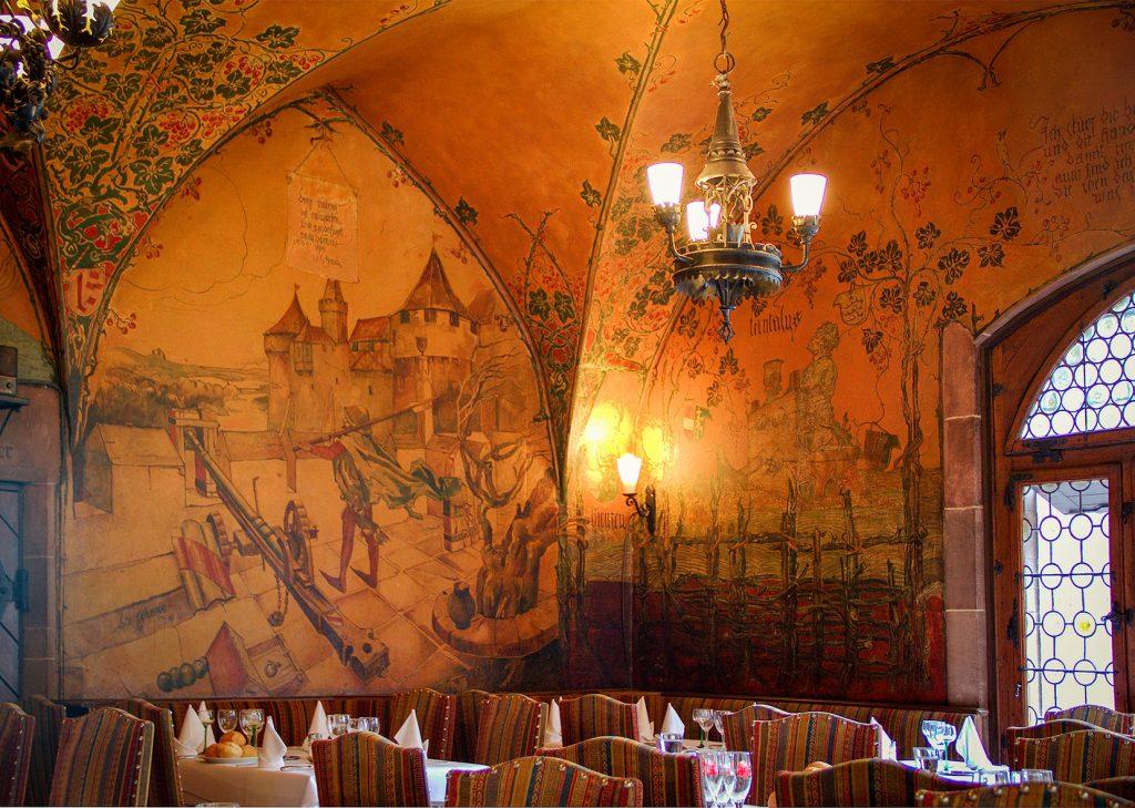 Leo Schnug. Trompe l'œil dans l'Escalade d'Illusions à la Maison Kammerzell. Fresque de Roland Perret. illusions-murales.com