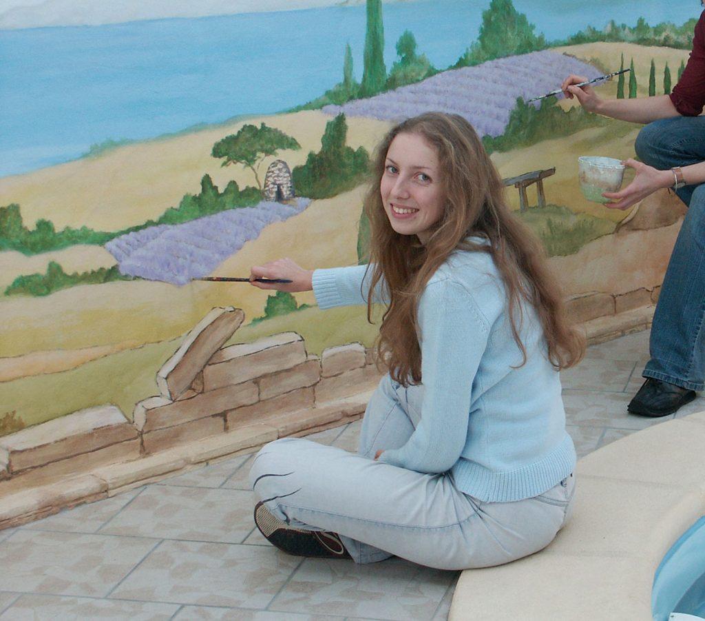 Sourya Perret peignant  une fresque provençale pour une piscine privée. Fresque de Roland Perret. illusions-murales.com